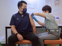 A visitor receives a shot of the Pfizer vaccine at the Tokyo Vaccination Centre (Stanislav Kogiku/AP)