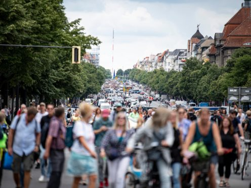 Demonstrators walk along Bismarckstrasse in Berlin, Sunday Aug. 1, 2021, during a protest against coronavirus restrictions. (Fabian Sommer/dpa via AP)