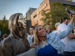 A woman takes a selfie with a newly unveiled statue of the mysterious developer of the Bitcoin digital currency in Budapest, Hungary (Bela Szandelszky/AP)
