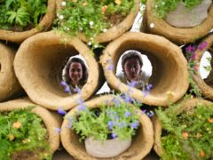 Designers Finbar Ward and Tilly Dallas look through bee hives formed from cylinders of clay, as part of RHS Chelsea Flower Show (Yui Mok/PA)