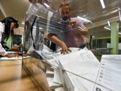 A member of an election commission pulls ballots out of a box preparing to count them at a polling station (AP)