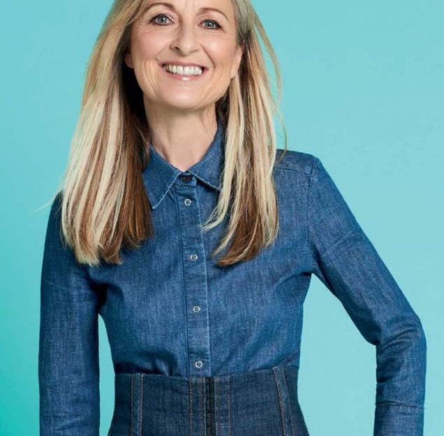 Fiona Phillips smiling at the camera on blue background