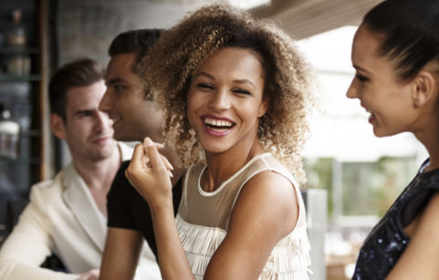 Woman laughing with friends at bar