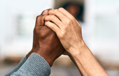 Two sets of hands clasping each other