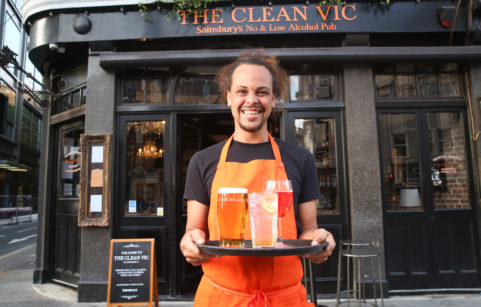 Man holding a tray of non-alcoholic drinks outside pub