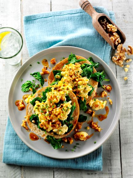 A bagel topped with scrambled egg, walnuts and paprika