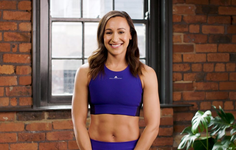 Former Olympic athlete Dame Jessica Ennis-Hill poses in front of a brick wall wearing dark blue activewear
