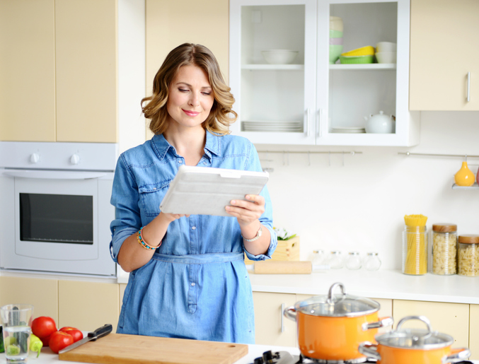 Woman in kitchen using tablet