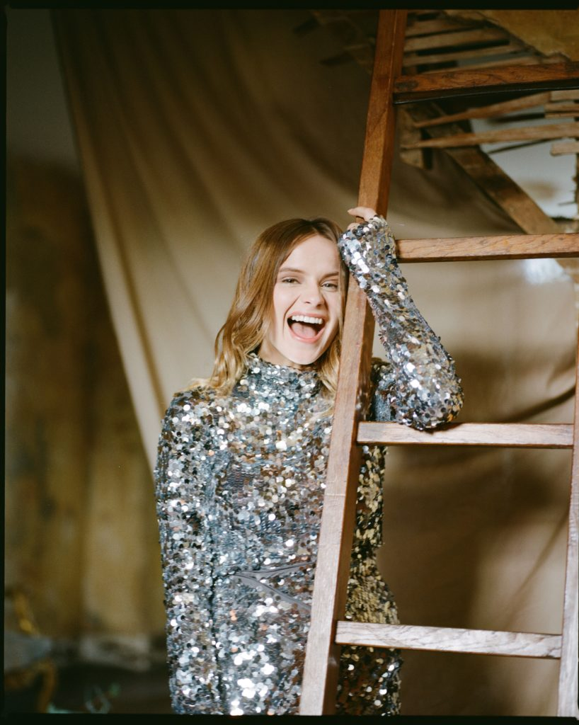 Gabrielle Aplin smiles in a silver sequin dress holding onto a wooden ladder
