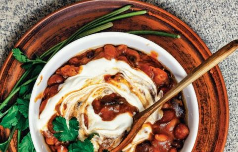 Vegan chilli con carne in a white bowl with wooden spoon