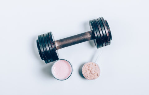 Whey protein drink in a glass next to a dumbbell weighr