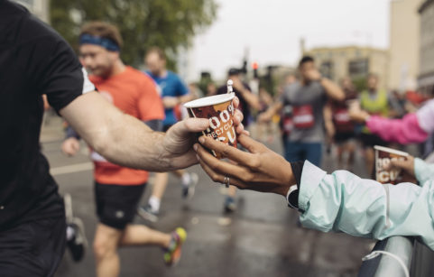 Runner being handed a cardboard cup of water on race