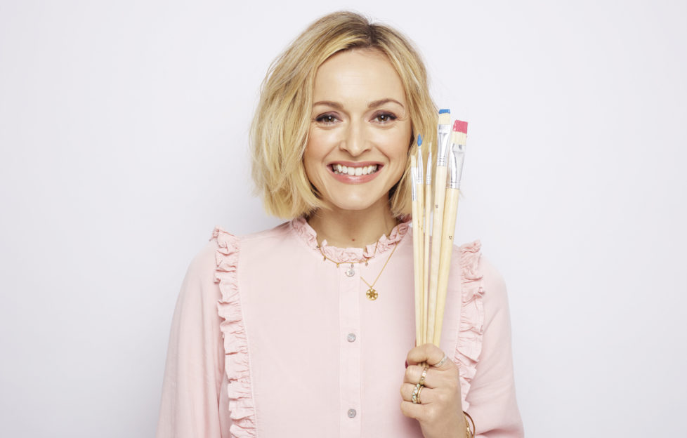 Fearne Cotton smiling and holding a set of paint brushes