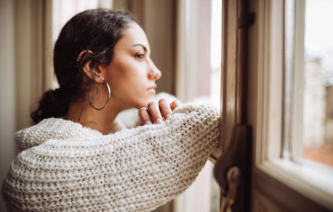 Millennial woman looking out the window feeling lonely