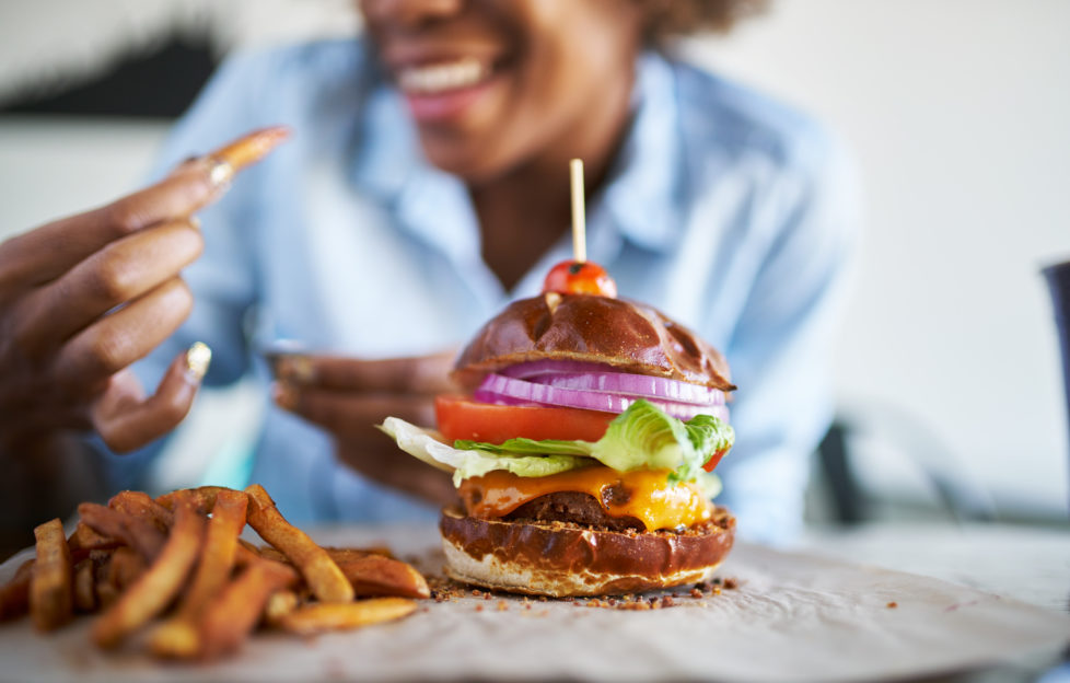 Woman getting ready to enjoy a burger and chips at the weekend