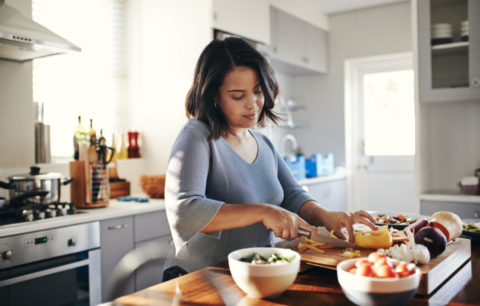 Young mum cooking her favourite dish to boost her wellbeing