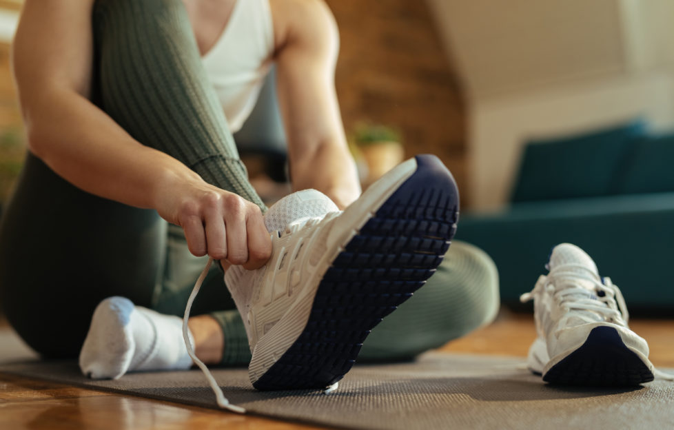 Woman putting on trainers for indoor workout