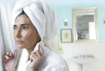 Woman with towel on head looking out bathroom window.