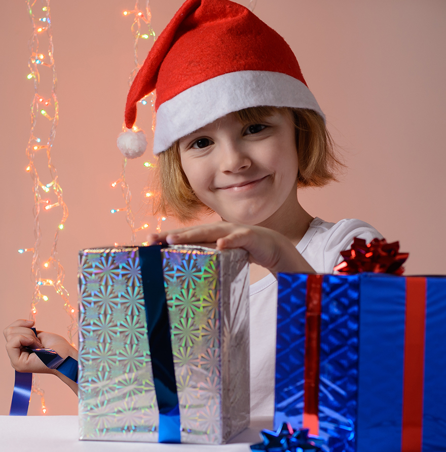 A happy girl in a Santa hat wrapping presents