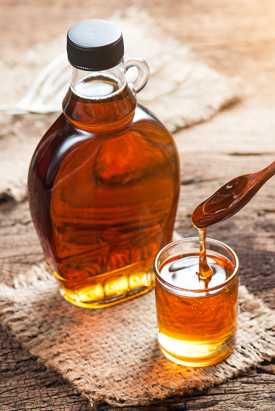 maple syrup, a natural sweetener, in a glass bottle on a wooden table