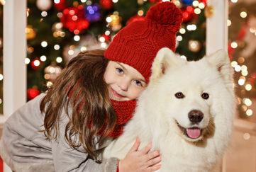 Dog and girl with Xmas tree in background Pic: Rex/Shutterstock