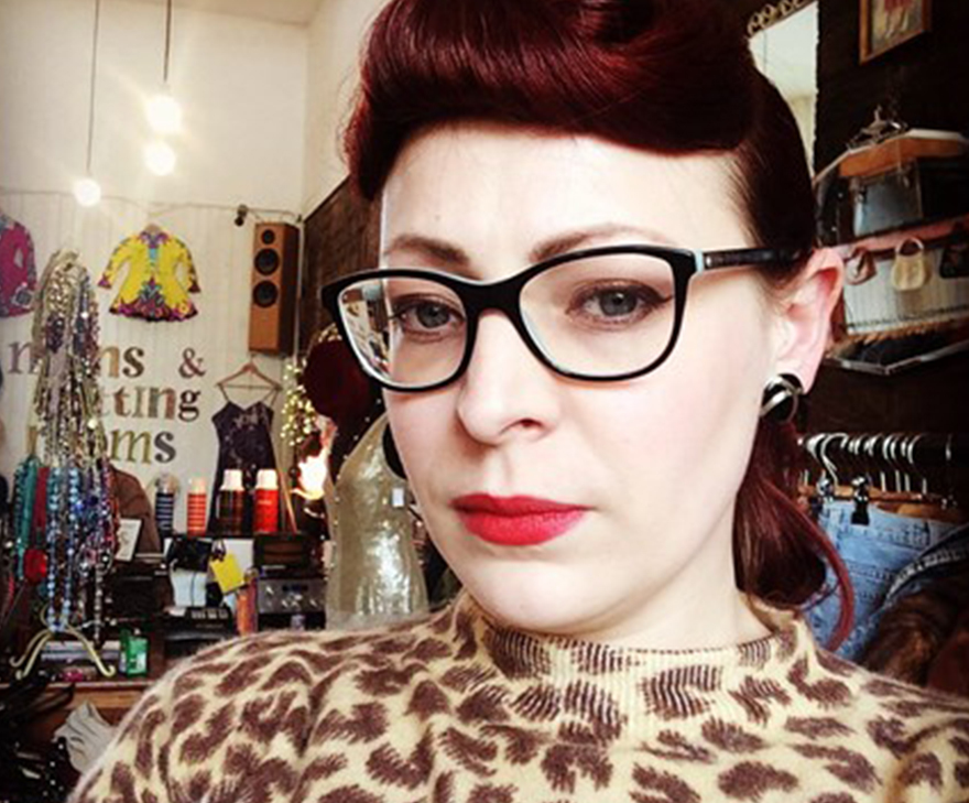 Carey Lander, a stylish young woman in dark framed glasses and red lipstick