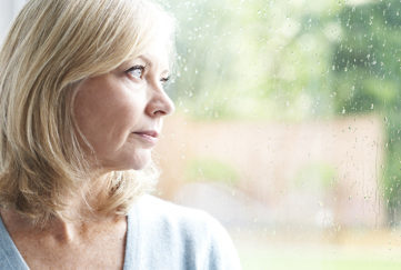 Sad Mature Woman Looking Out Of Window