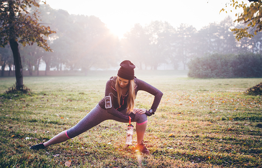 Woman in sports gear and woolly hat, stretching in a park, early morning light