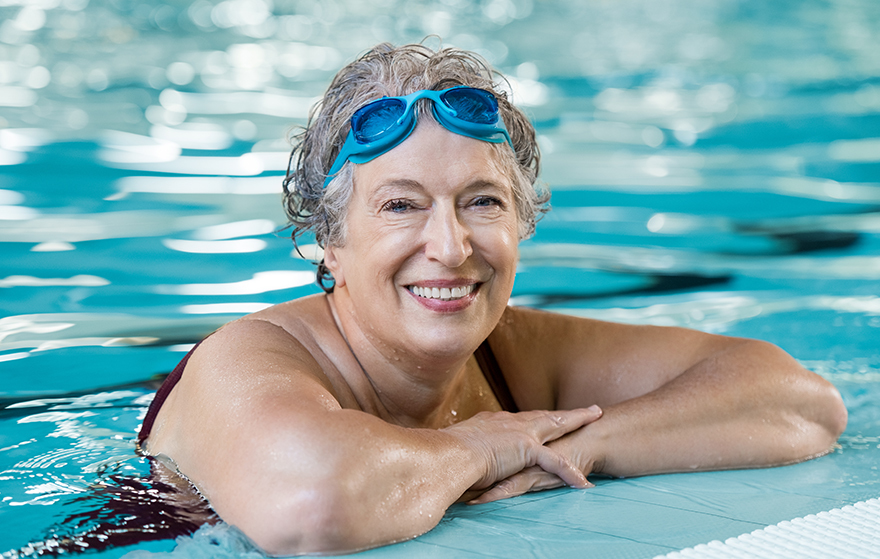 Smiling mature woman at the edge of a swimming pool