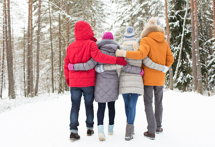 Reduce Christmas stress. A family walking through a snowy wood, arms round each other