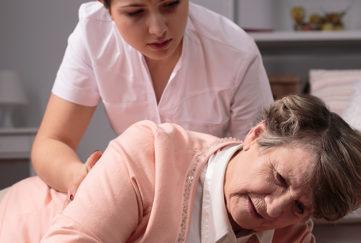 Helpful worried caregiver and senior woman on floor