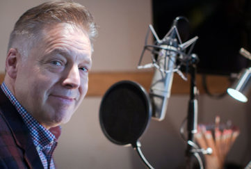 Stroke survivor DJ Mike Goodier at a radio microphone.