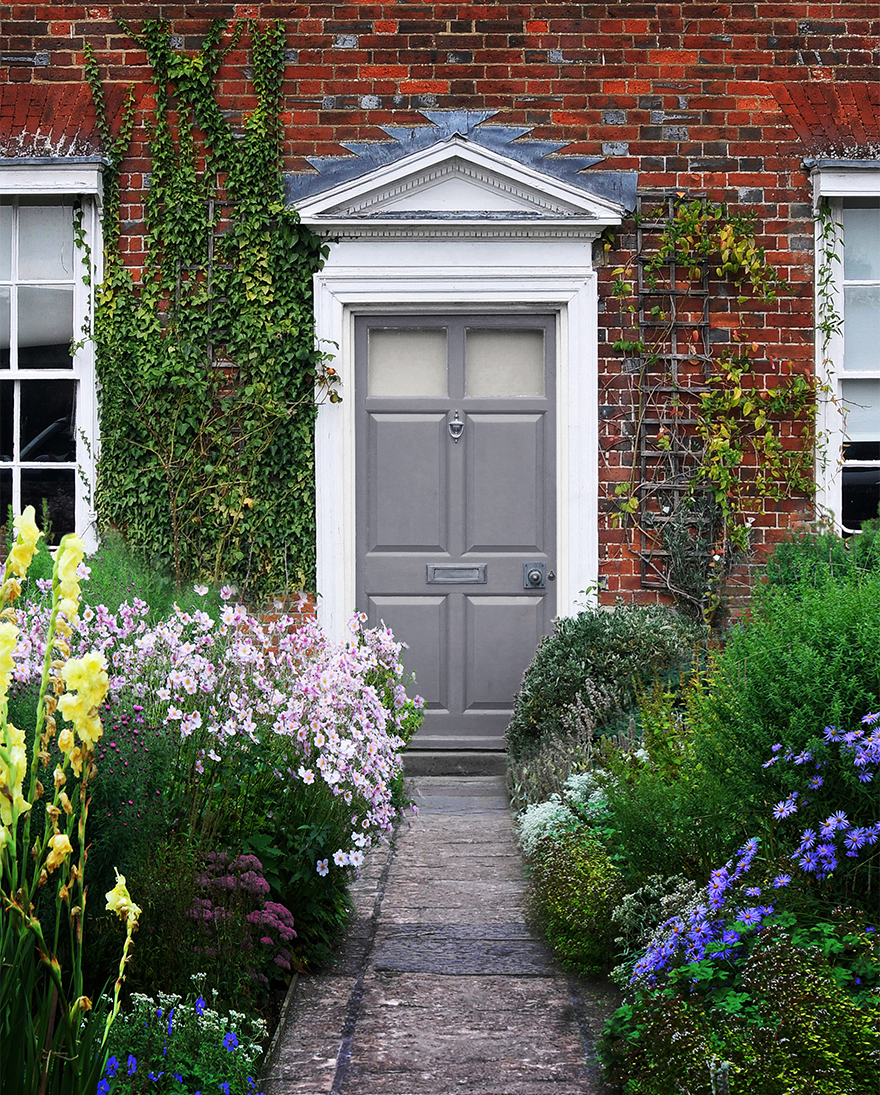 Grey-painted front door of period property with tall flowers either side of the path