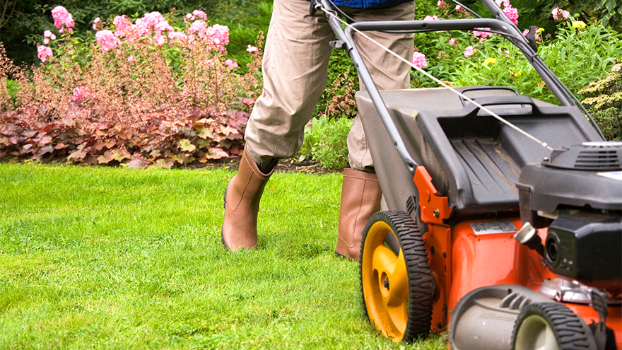 Lower half of person, in trousers and boots, pushing a lawnmower