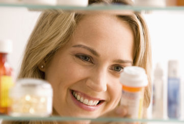 Young woman looking through medicine cabinet and checking date on tablets