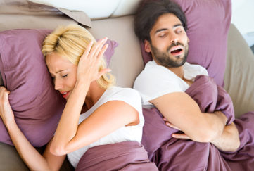 Woman covering ears while man snores in sleep.