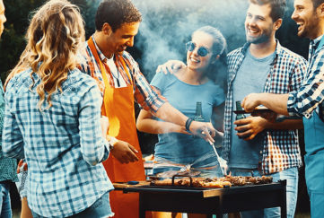 Closeup side view of group of mid 20's people having backyard barbecue party. There are three guys and four girls gathered around heavily smoking grill and sipping cold beer. One of the guys is being today's chef. Toned image, mild contrast, back lit. Pic: Istockphoto