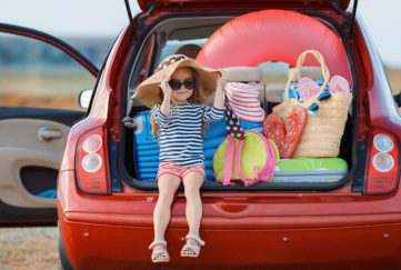 Small girl sitting in open boot of car at seaside