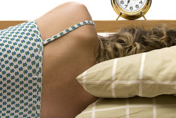 Women sleeping on stripped pillows facing away from camera