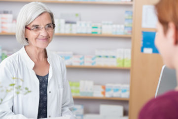 Pharmacist giving advice to woman in shop