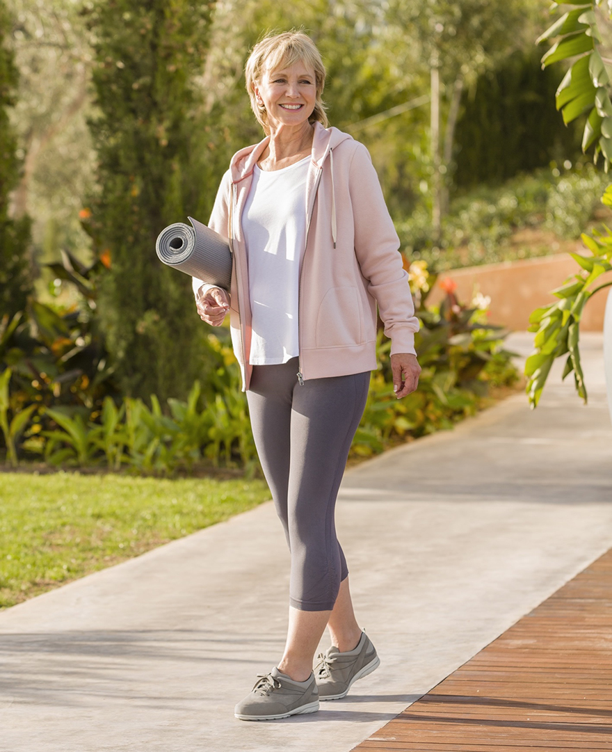 Woman walking with grey yoga mat