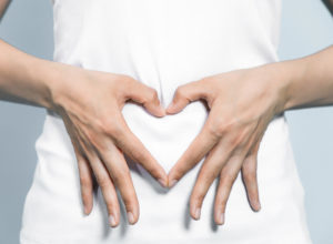 Woman making heart shape over tummy with hands