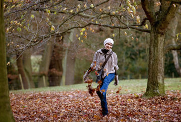Woman kicking leaves in autumn time