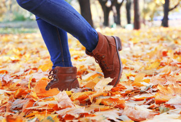 Woman in jeans and boots kicking leaves