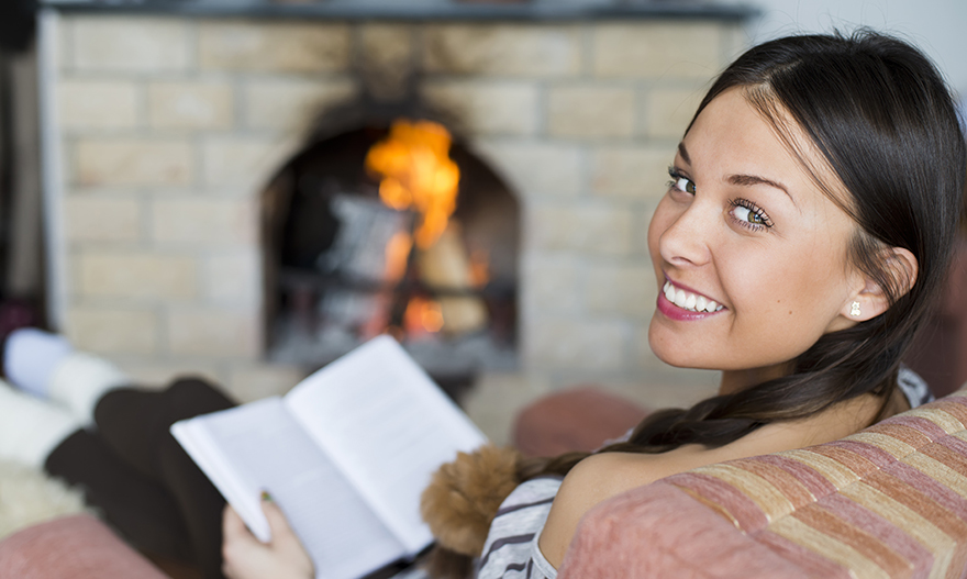 Young woman readinga book near fireplace