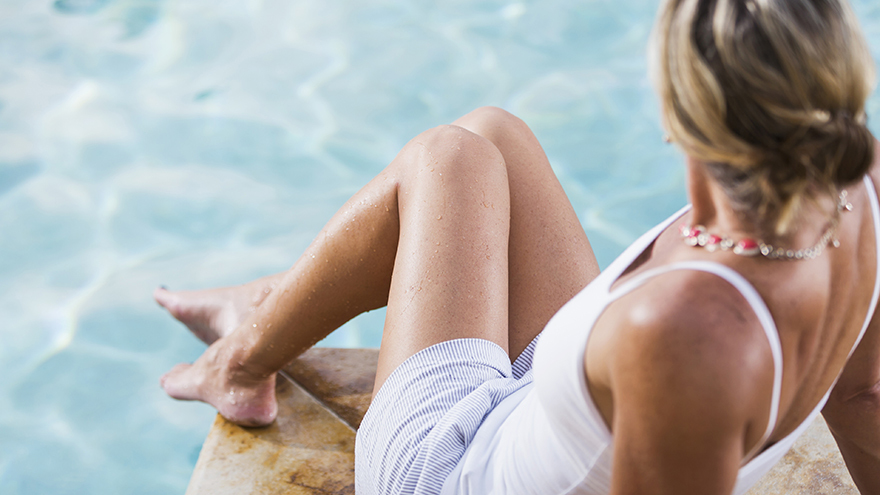 High angle rear view of a mature woman sitting and relaxing at the edge of a swimming pool.