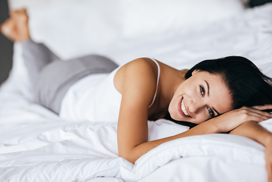 Young woman looking at camera and smiling while lying on the bed at home