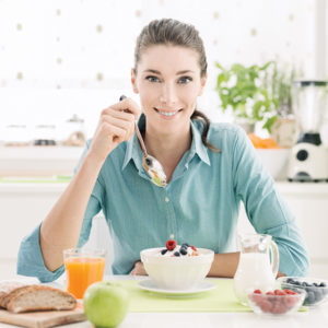 Smiling woman having a relaxing healthy breakfast at home