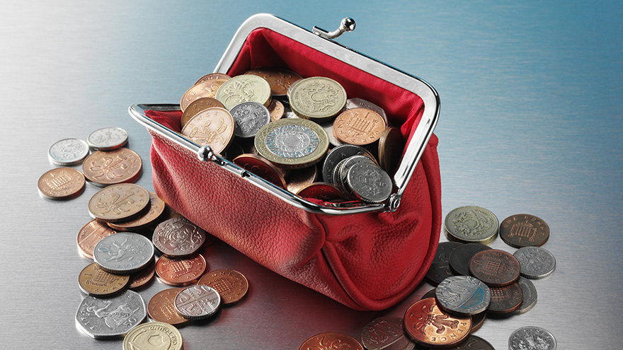 Purse full of British money on a stainless steel background.