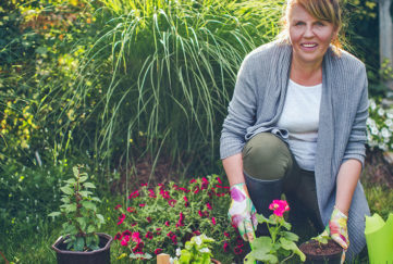 Portrait of smiling mid-adult woman who is gardening and watering the plants